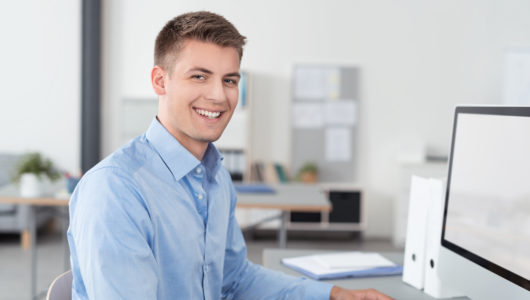 lächelnder mann arbeitet im büro