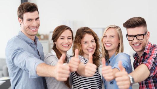 fünf junge leute zeigen daumen hoch
