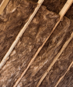 Brown glass wool in a wooden frame on a inclined wall near the wooden ceiling in a private house. Warming the house with fiberglass.